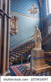 GLASCOW/SCOTLAND - JUNE 29, 2017: An interior view of an elegant blue-wallpapered room with staircase and Adam Smith statue in the Main Building on the historic ancient University of Glascow campus.