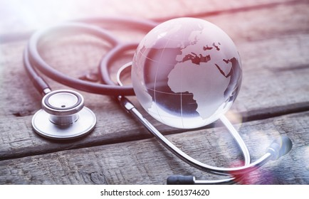 glasd global and stethoscope on wood table, healthcare concept, world environment day, process vintage tone. Elements of this image are furnished by NASA