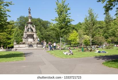 Glasgow, Scotland - 26 May, 2018: People sunbathing next to the Stewart Memorial Fountain in Kelvingrove Park.
