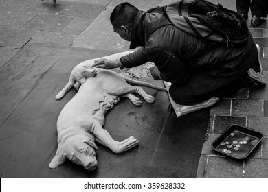 Glasgow, Scotland - April 10, 2015:Street artist is creating a dog using dry sand in the middle of the street in the Center of Glasgow in Scotland UK 2015