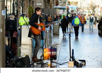 GLASGOW, SCOTLAND - JANUARY 22, 2016: A young man busking with guitar in Buchanan Street, Glasgow, Scotland.