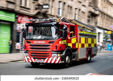 GLASGOW, SCOTLAND - JULY 31, 2019: A red Scania P280 fire truck in the streets of Glasgow driving very quickly with a strong motion blur effect with focus on Scania logo