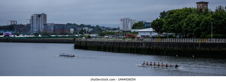 Glasgow, Scotland - May 25 2019: Edinburgh University rowing team lead Glasgow University rowing team during the Scottish Boat Race on the river Clyde.