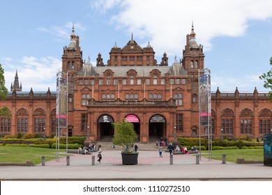 GLASGOW, SCOTLAND - MAY 26, 2018: Kelvingrove Art Gallery and Museum facade with blue sky and clouds and people walking on the street on a summer day.