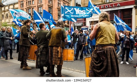 Glasgow, Scotland; May 4th 2019: Independence for Scotland march. Three drummers and a piper playing as walkers pass waving the Scottish flag, the Saltire.