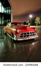 GLASGOW, SCOTLAND - OCTOBER 10: a Pontiac 1950 classic car reflecting on the rain soaked ground at night on October 10, 2014 in Glasgow, Scotland.