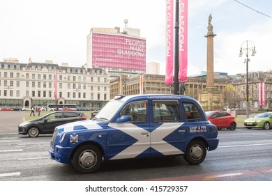 GLASGOW, SCOTLAND, UK - 27 APRIL 2016: Taxi painted with St Andrew's Cross, the National Flag of Scotland driving through George Square, Glasgow