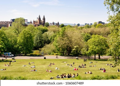 Glasgow, Scotland, UK - June 10 2015: Young people, students of the University of Glasgow enjoying a warm sunny day on the lawns of Kelvingrove park, Kelvingrove Art Gallery and Museum in the backgrou