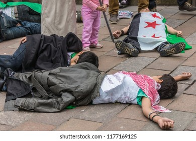 Glasgow, Scotland, UK - June 17, 2012: Syrians protest Bashar al-Assad war crimes near Donald Dewar statue. Children pretending to be killed by Syrian regime.