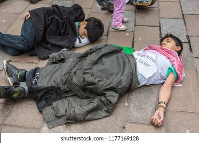 Glasgow, Scotland, UK - June 17, 2012: Syrians protest Bashar al-Assad war crimes near Donald Dewar statue. Children flat on floor pretending to be dead.