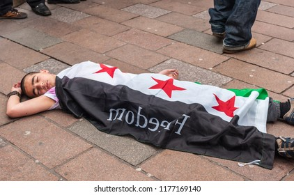 Glasgow, Scotland, UK - June 17, 2012: Syrians protest Bashar al-Assad war crimes near Donald Dewar statue. Closeup of Child flat on floor pretending to be dead.