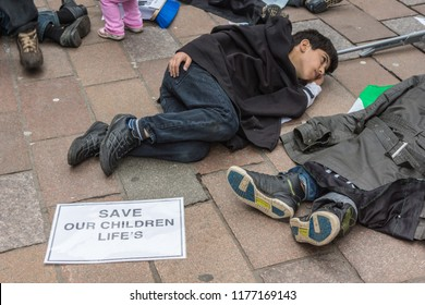 Glasgow, Scotland, UK - June 17, 2012: Syrians protest Bashar al-Assad war crimes near Donald Dewar statue. Closeup of Child flat on floor pretending to be dead.