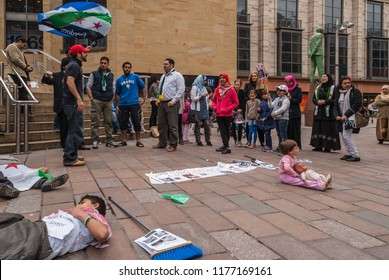 Glasgow, Scotland, UK - June 17, 2012: Syrians protest Bashar al-Assad war crimes near Donald Dewar statue. Group of men, women and children yelling slogans. Children pretend to be dead on ground.