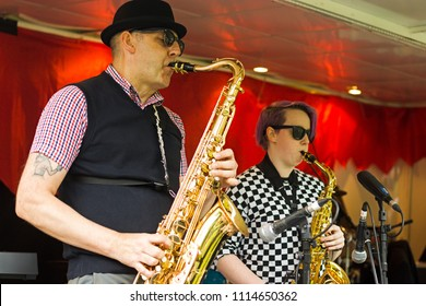 Glasgow, Scotland / UK - June 17th 2018: Male and Female Saxophone players in Ska band, playing in Kelvingrove Park as part of West End Festival