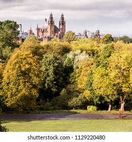 Glasgow, Scotland, UK - September 30, 2017: A pedestrian walks through Kelvingrove Park in the west end of Glasgow on a sunny autumn day, with autumn trees and Kelvingrove Museum behind.
