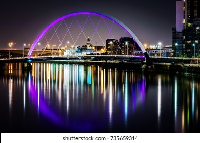 GLASGOW, UK - AUGUST 16, 2017 - modern architecture with skyscrapers and illuminated bridges reflected on the river at night in the industrial area and the harbor city of Glasgow in Scotland