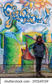 GLASGOW, UK, circa March 2014: Street art in Glasgow West End, near Byres Road. Unidentified hipster girl standing next to a wall of graffiti with the writing Glasgow on the top.