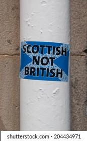 "GLASGOW, UK, July 2014: Scottish independence: ""Scottish not British"" sticker on a white pole in a Scottish street in Edinburgh"