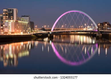 Glasgow/Scotland - September 20 2016: The Clyde Arc lit up in violet and surrounding buildings, reflected in the Clyde River at night