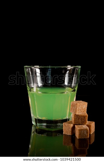 A glass with absinth on a black reflecting surface
