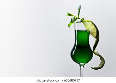 Glass of absinthe garnished with a slice of lime and mint leaves . Copy space .
