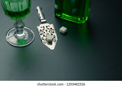 a glass of absinthe, a stainless steel slotted spoon with the sugar cubes and the absinthe bottle on the table