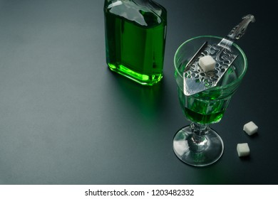 a glass of absinthe and a stainless steel slotted spoon with the sugar cubes, the absinthe bottle on the table
