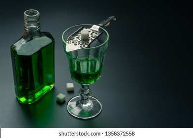 a glass of absinthe and a stainless steel slotted spoon with the sugar cubes, the absinthe bottle on the table, selective focus