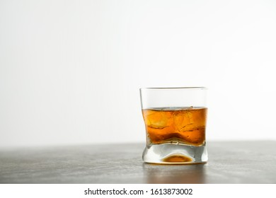 Glass of aged golden whiskey with ice cubes on the table. Amber colored alcohol beverage with rocks at the bar