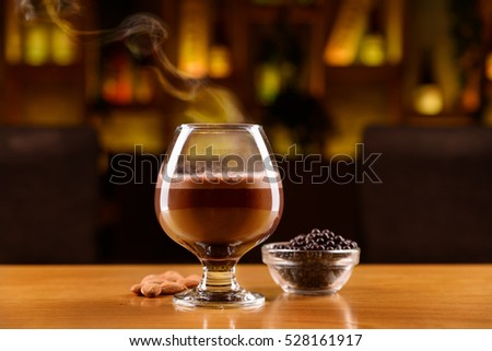Glass with alcohol, coffee, cocoa and chocolate on a layers. Almonds and chocolate balls on a wooden table.