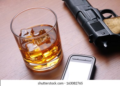 A glass of alcoholic drink, a cell phone and a handgun over a wooden table