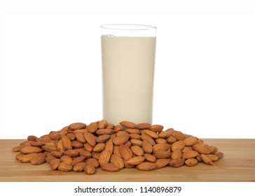 Glass of almond milk on a wood table surrounded by whole raw almonds, isolated on white background. Almond milk is lower in calories than other milks and cholesterol free, lactose free.