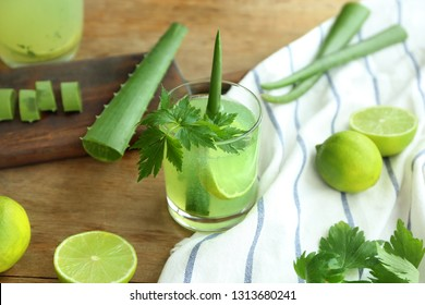 Glass of aloe vera cocktail with ingredients on wooden table