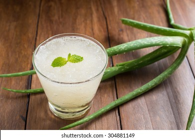 Glass of aloe vera juice on a wooden table
