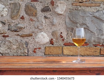 Glass of amber white wine on a rustic wooden table with an old Stone wall behind. Background for copy space