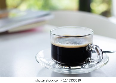 Glass of americano fresh made dark black strong coffee on wooden board table in morning.