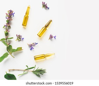 Glass ampoules and medicinal herbs on a white background, top view, flat lay, copy space. Alternative medicine or organic cosmetics concept, free space for text.
