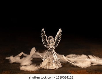 Glass angel with fallen feathers on a dark background