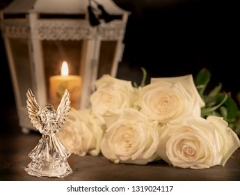 Glass angel with fallen feathers, roses and candle on a dark background