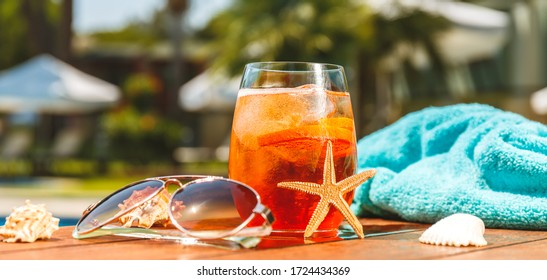 Glass of aperol spritz or negroni cocktail with seashells, towel and sunglasses at the summer patio. Vacation, summer, holiday, luxury resort concept. Horizontal wide screen banner format