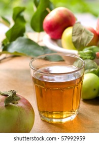 Glass of apple juice with apples in the background.