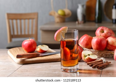 Glass of apple juice , apples and cinnamon sticks on a kitchen table.