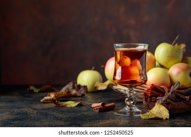 Glass of apple juice or cider with juicy apples and cinnamon sticks on a kitchen table.