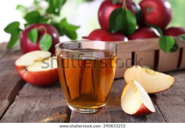 Glass of apple juice with red apples on wooden table, closeup