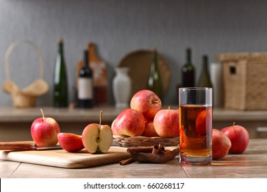 Glass of apple juice and ripe apples on a kitchen table