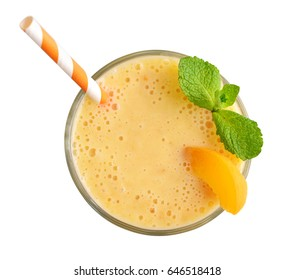 Glass of apricot milkshake or smoothie with drinking straw and mint leaves  isolated on white background, top view