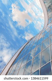 Glass architecture with smooth lines against the sky and clouds