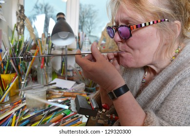 Glass Artist in her workshop. Glassblowing a piece of jewellery.