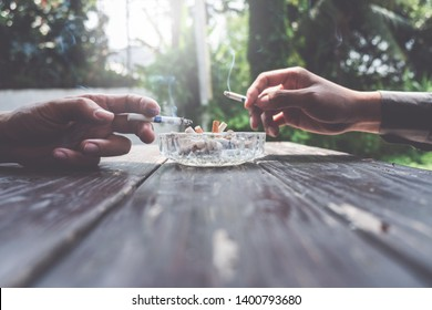 Glass ashtray full of cigarette ash and butts on the table, two hand holding cigarette.