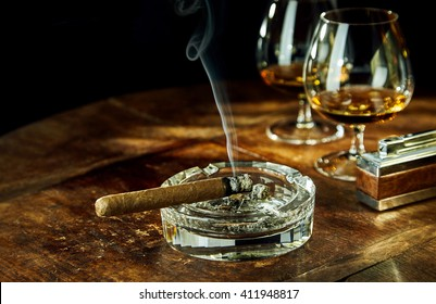 Glass ashtray with smoking cigar by two glasses filled with bourbon besides fancy lighter on a wood table